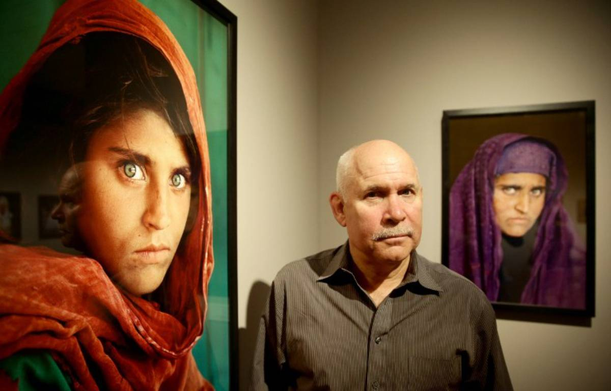 Steve Curry pose devant le cliché de Sharbat Gula – ULRICH PERREY / DPA / AFP