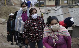 Des femmes attendent une distribution de nourriture, à Lima au Pérou le 27 mai 2020.