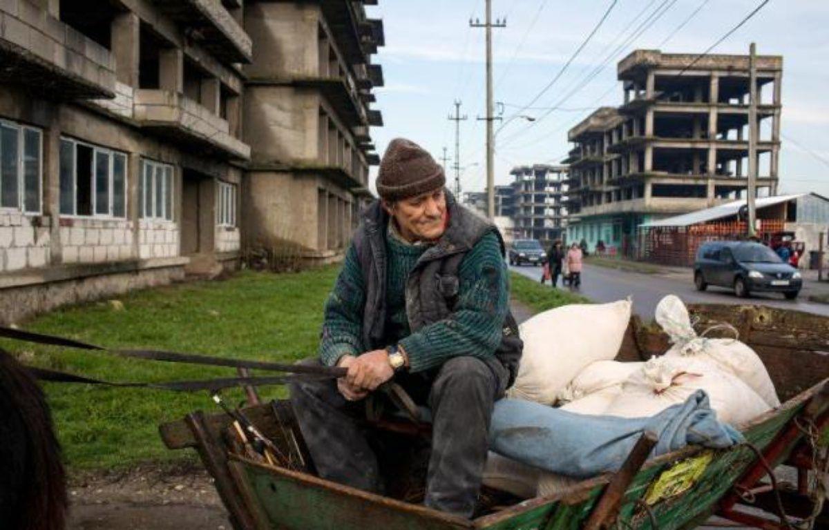 Un homme est assis dans sa charrette au milieu d'une rue de Zimnicea (130 km sud-est de Bucarest) ville ravagée par la pauvreté, 25 ans après la révolution roumaine – Andrei Pungovschi AFP