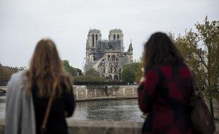 Des passantes devant Notre-Dame de Paris le 16 avril 2019 au lendemain de l'incendie qui a ravagé la cathédrale.