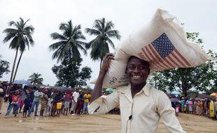 Un homme porte un sac du Programme alimentaire mondial à Dolo, au Libéria, le 2 septembre 2014.