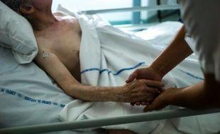 Une infirmière tient la main d'un patient dans une unité de soins palliatifs d'Argentueil, le 22 juillet 2013
