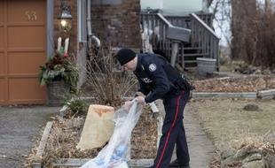 Un policier enquête dans le jardin d'une maison où Bruce Mc Arthur, jardinier-paysagiste de Toronto, accusé du meurtre de 6 homosexuels, travaillait.