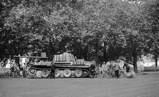 Des badauds découvrent un char panther abandonné par les Allemands sur les quais de la Seine, entre le Pont Neuf et le Pont Notre-Dame, aux alentours du 19 août, quelques jours avant la Libération de Paris, le 25 août 1944