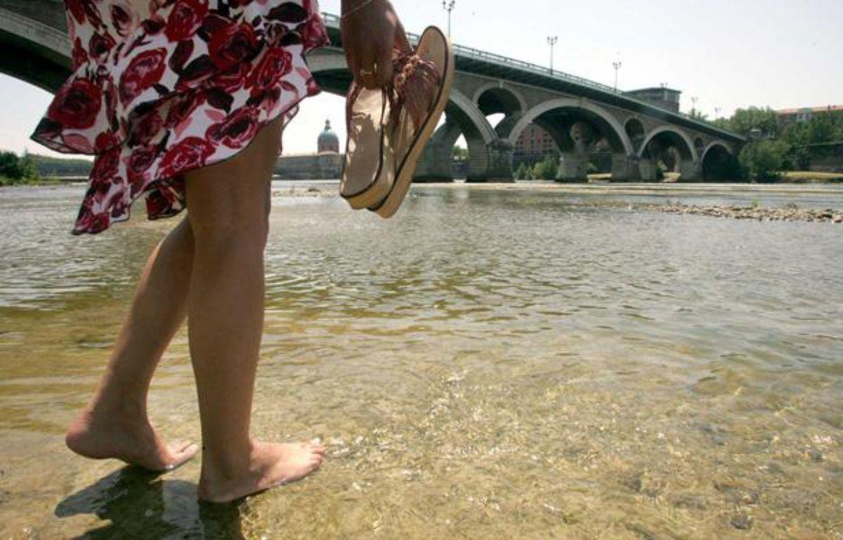 Une femme marche pieds nus dans la Garonne, à Toulouse. – BORDAS/SIPA