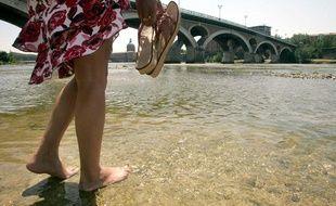 Une femme marche pieds nus dans la Garonne, à Toulouse.