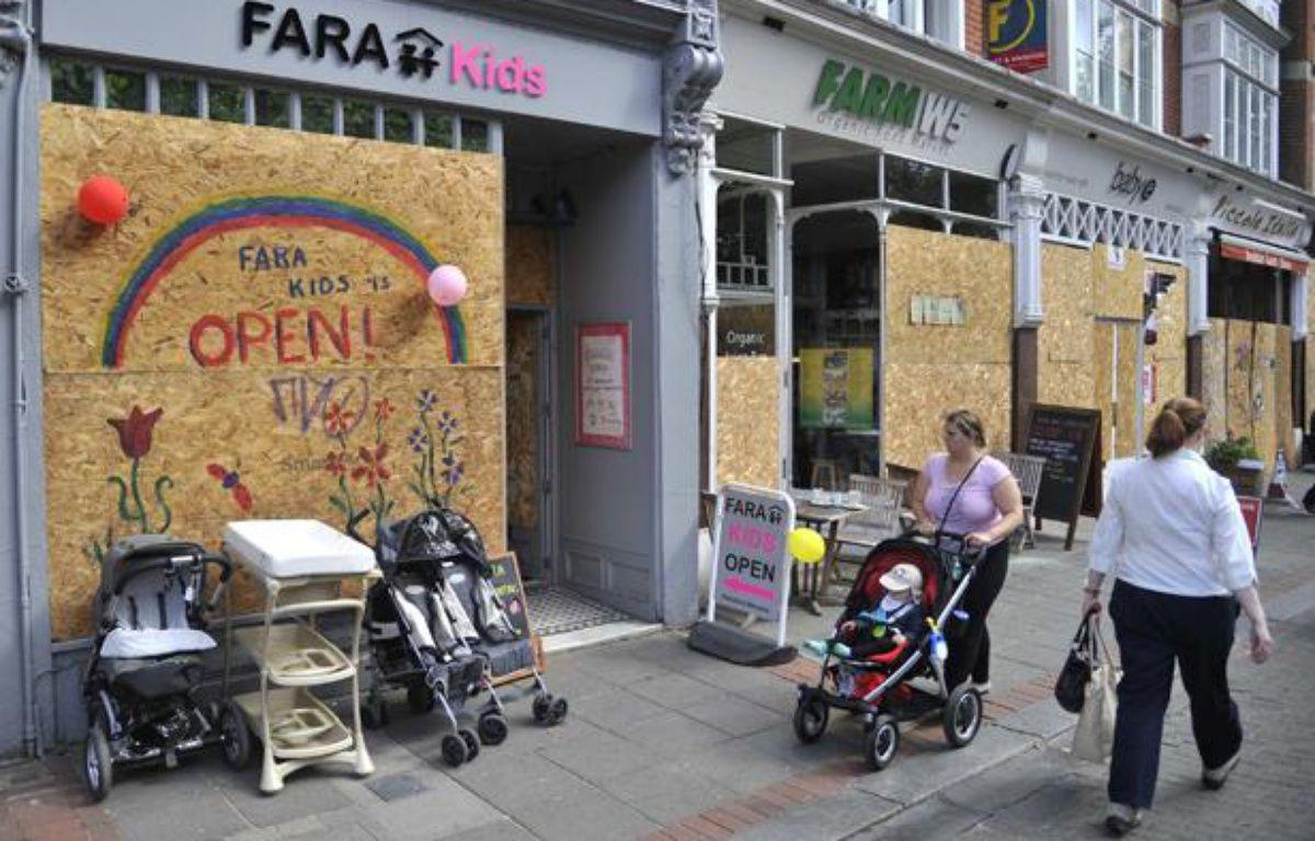 Une femme passe près d'un magasin vandalisé à Londres le 10 août 2011. – REUTERS/Toby Melville