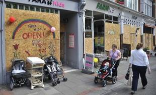 Une femme passe près d'un magasin vandalisé à Londres le 10 août 2011.