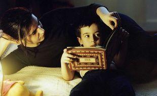 Un jeune garçon lit avec sa mère - Illustration