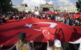 Des manifestants tiennent un drapeau géant de la Turquie en face de la porte de Brandebourg à Berlin , Allemagne , le mercredi 1er Juin , 2016. Ils protestent contre une résolution du parlement fédéral allemand qui reconnait le génocide arménien.