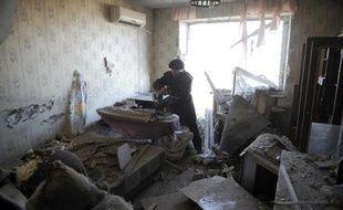 Une femme récupère des affaires à l'intérieur de son appartement dévasté par un bombardement, le 5 novembre 2014 à Donetsk, dans l'Est de l'Ukraine