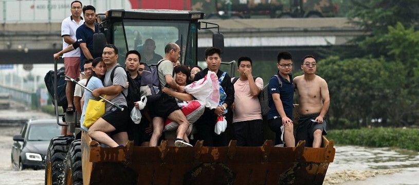 Des habitants de Zhengzhou, en Chine, ont pris place sur un tractopelle pour traverser une rue inondée à la suite de fortes pluies qui ont provoqué des inondations et coûté la vie à au moins 33 personnes mi-juillet.