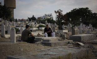 Un père et un fils palestiniens sur la tombe d'un autre fils, mort après une attaque israélienne dans la bande de Gaza, le 28 juillet 2014.