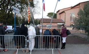 Des habitants signent le livre de condoléances devant la mairie de Saint-Feliu d'Avall, le 15 décembre.