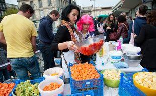 """Bordeaux, 7 avril 2013. - """"Disco Soupe"""" organisee au Marche des Capucins, a Bordeaux, pour lutter contre le gaspillage. Les Disco Soupe sont des sessions collectives et ouvertes a tous d'epluchage de fruits et legumes mis au rebut, invendus ou de troisième main dans une ambiance festive. Les rebuts sont ensuite cuisines et distribues au grand public gratuitement. L'initiative tend a lutter contre le gaspillage alimentaire en montrant aux gens que des fruits et legumes, meme """"moches"""", pas standards, sont bons. - Phoot : Sebastien Ortola"""