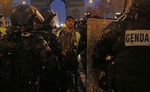 Un «gilet jaune» tend une fleur aux gendarmes sur l'avenue des Champs-Elysées à Paris ce samedi 15 décembre.