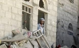 Un homme observe les dégâts causés par un raid aérien de la coalition, à Sanaa, le 1er mai 2015
