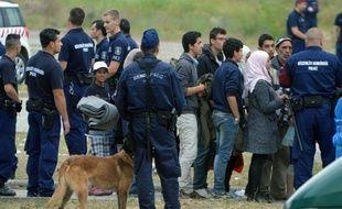 Des demandeurs d'asile attendent un bus devant les emmener à Röszke, en Hongrie, en juin 2015