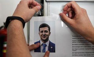 Un membre d'une commission locale pour les élections en Ukraine affiche un portrait du comédien Volodymyr Zelensky favori des sondages pour le second tour de l'élection présidentielle en Ukraine dimanche 21 avril 2019.
