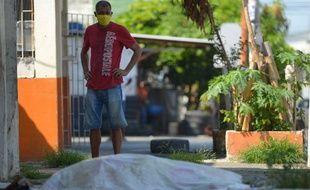 Un homme regarde l'un des corps laissé ici, à l'abandon depuis trois jours devant une clinique de Guayaquil.