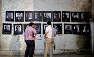 Des membres de l'association des Anciens Prisonniers Politiques du Stade National regardent des photos de la période de la dictature de Pinochet exposées dans le stade, le 10 février 2015 à Santiago