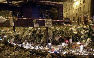 Des fleurs et bougies déposées devant un restaurant du 11e arrondissement de Paris en hommage aux victimes des attentats, le 16 novembre 2015