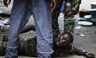 Un ancien membre des forces pro-Gbagbo entre les mains des hommes fidèles à Ouattara à Abidjan le 16 avril 2011.