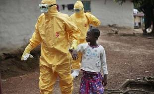 FILE - In this Sept. 30, 2014, file photo, Nine-year-old Nowa Paye is taken to an ambulance after showing signs of the Ebola infection in the village of Freeman Reserve, about 30 miles north of Monrovia, Liberia. (AP Photo/Jerome Delay, File)/NY823/135872493452/SEPT. 30, 2014 FILE PHOTO/1412171722