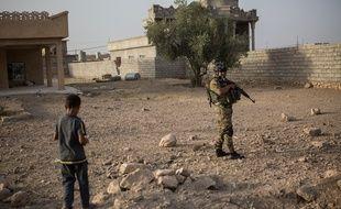 Un soldat des forces spéciales avec un enfant dans la banlieue de Mossoul le 5 août 2016.