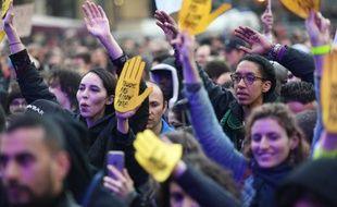 Des manifestants arborant es mains flanquées du slogan