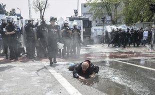 Un homme essaie de se relever après avoir été renversé par des jets de canons à eau utilisés par la police turque pour disperser une manifestation, le 1er mai 2015 à Istanbul
