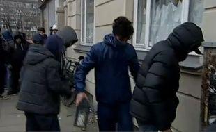Le 16 février 2015, de jeunes musulmans retirent les fleurs déposées devant l'immeuble où est mort le suspect des fusillades de Copenhague, au Danemark.