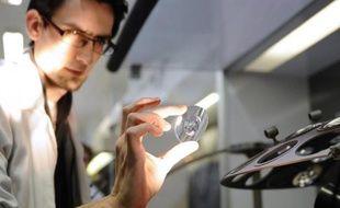 Un employé contrôle un verre avant de lui appliquer un traitement anti-reflets, au laboratoire d'Essilor, à Ligny-en-Barrois (Meuse), le 19 janvier 2015