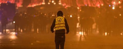 "A protester wearing a Yellow Vest (Gilets jaunes) faces riot police during a demonstration of the 'Yellow Vests' (Gilets Jaunes)   against rising costs of living on the Champs Elysees avenue in Paris on December 8, 2018. - Paris was on high alert on December 8 with major security measures in place ahead of fresh ""yellow vest"" protests which authorities fear could turn violent for a second weekend in a row. (Photo by Lucas BARIOULET / AFP)"