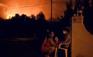 Les incendies font rage au Portugal. Une femme tente de rassurer son voisin.