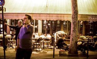 Des personnes s'occupent d'une personnes allongée au sol après les tirs qui ont visé le café «La bonne bière», le 13 novembre 2015