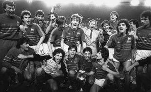 Les joueurs de l'équipe de France posant autour du trophée de l'Euro 1984, après une victoire en finale face à l'Espagne (2-0), le 27 juin 1984, au Parc des Princes, à Paris.