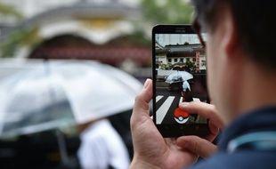 Un homme joue avec le jeu Pokemon Go sur son téléphone à Tokyo le 22 juillet 2016