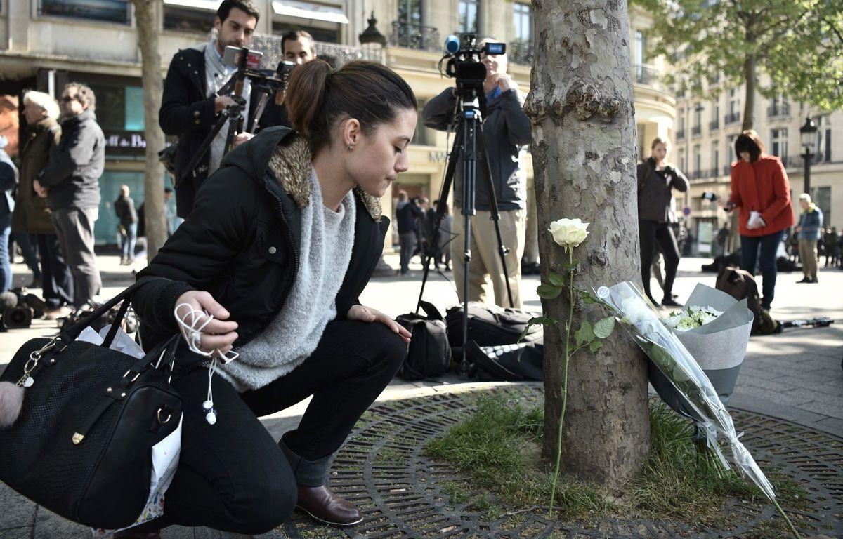 Sur les Champs-Elysées vendredi 21 avril 2017, certains passants déposent des fleurs à l'endroit où un policier a été tué. – AFP