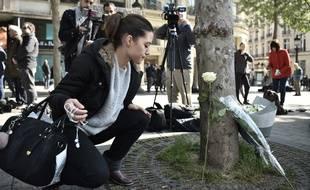 Sur les Champs-Elysées vendredi 21 avril 2017, certains passants déposent des fleurs à l'endroit où un policier a été tué.