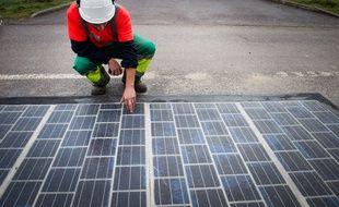 Un ingénieur teste un panneau photovoltaïque posé sur une route (Illustration).