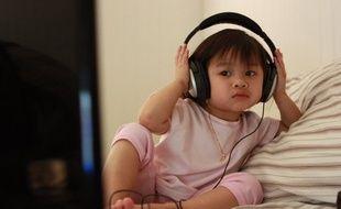 Un enfant devant la télévision, un casque sur les oreilles.