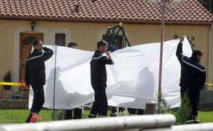 Des gendarmes masquent d'un drap blanc, le 14 avril 2009 à Cabanac, un brancard transportant le corps d'une des victimes, l'épouse et les deux des enfants tués la nuit précédente par leur mari et père, un policier. Thierry Gourjault, 42 ans, a ensuite pris la fuite.