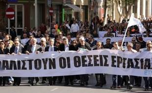 Employees of the bank hold banners as they march towards the parliament on April 4, 2013 during a demonstration in the Cypriot capital, Nicosia, over fears that pensions may be at risk under Cyprus's bailout, as more details emerged of biting austerity measures imposed on the cash-strapped island. Bank employees' union ETYK called the two-hour work stoppage over concerns that pension funds at failed Laiki and at Bank of Cyprus are not being protected under the island's 10-billion-euro bailout deal with the IMF, European Commission and European Central Bank. AFP PHOTO / PATRICK BAZ