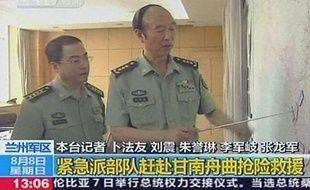 Deux militaires chinois montrent la provine de Gansu où un glissement de terrain a fait au moins 96 morts, dimanche 8 août.