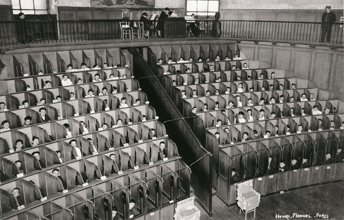 Détenus dans les box de la chapelle cellulaire de la Petite Roquette à Paris en 1930. – Henri Manuel