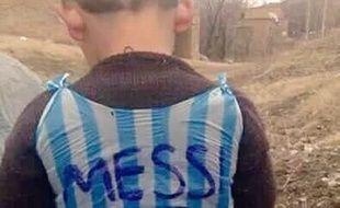 La photo d'un enfant avec un maillot de Lionel Messi fabriqué à partir d'un sac plastique.