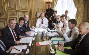 Photo du 11 avril 2014 montrant le Premier ministre Manuel Valls (gauche) entouré de ses ministres, face au patron des patrons Pierre Gattaz (d) et au vice-président du Medef Geoffroy Roux de Bezieux à Matignon