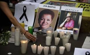 En mai 2017, des passants allument des bougies pour rendre hommes aux journalistes tués au Mexique, Miroslava Breach, à gauche et Javier Valdez lors d'une manifestation contre les assassinats de journalistes dans ce pays particulièrement dangereux pour les reporters.