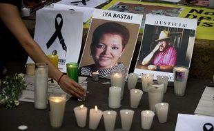 En mai 2017, des passants allument des bougies pour rendre hommage aux journalistes tués au Mexique, Miroslava Breach, à gauche et Javier Valdez lors d'une manifestation contre les assassinats de journalistes dans ce pays particulièrement dangereux pour les reporters.